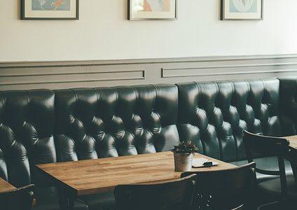 Restaurang med små bruna bord och en svart soffa längs med väggen